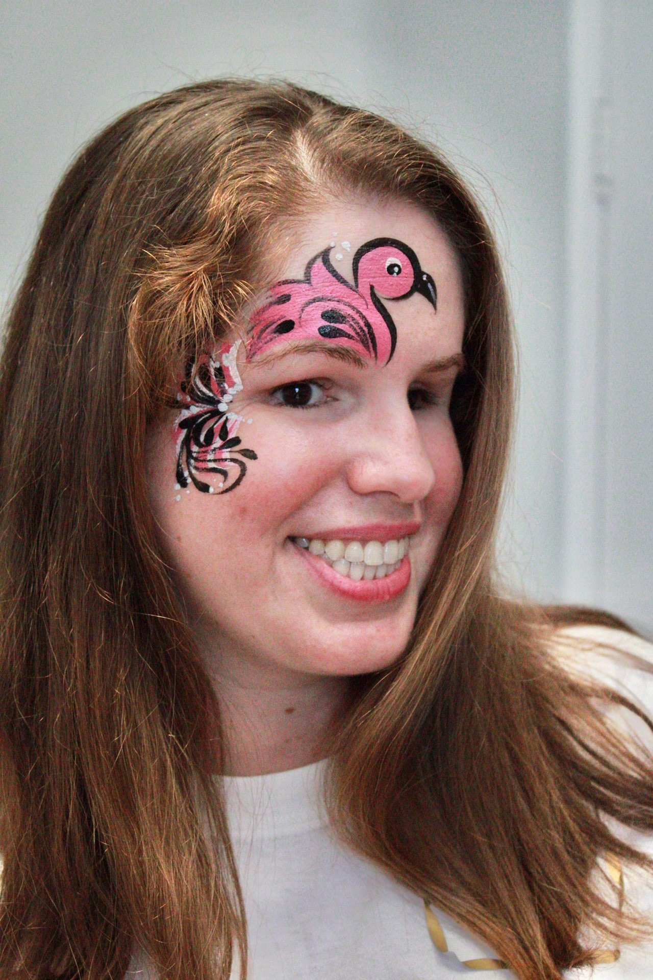 A young woman features a painted pink, black, and white flamingo over her right eye, and is flashing a bright, beautiful smile.