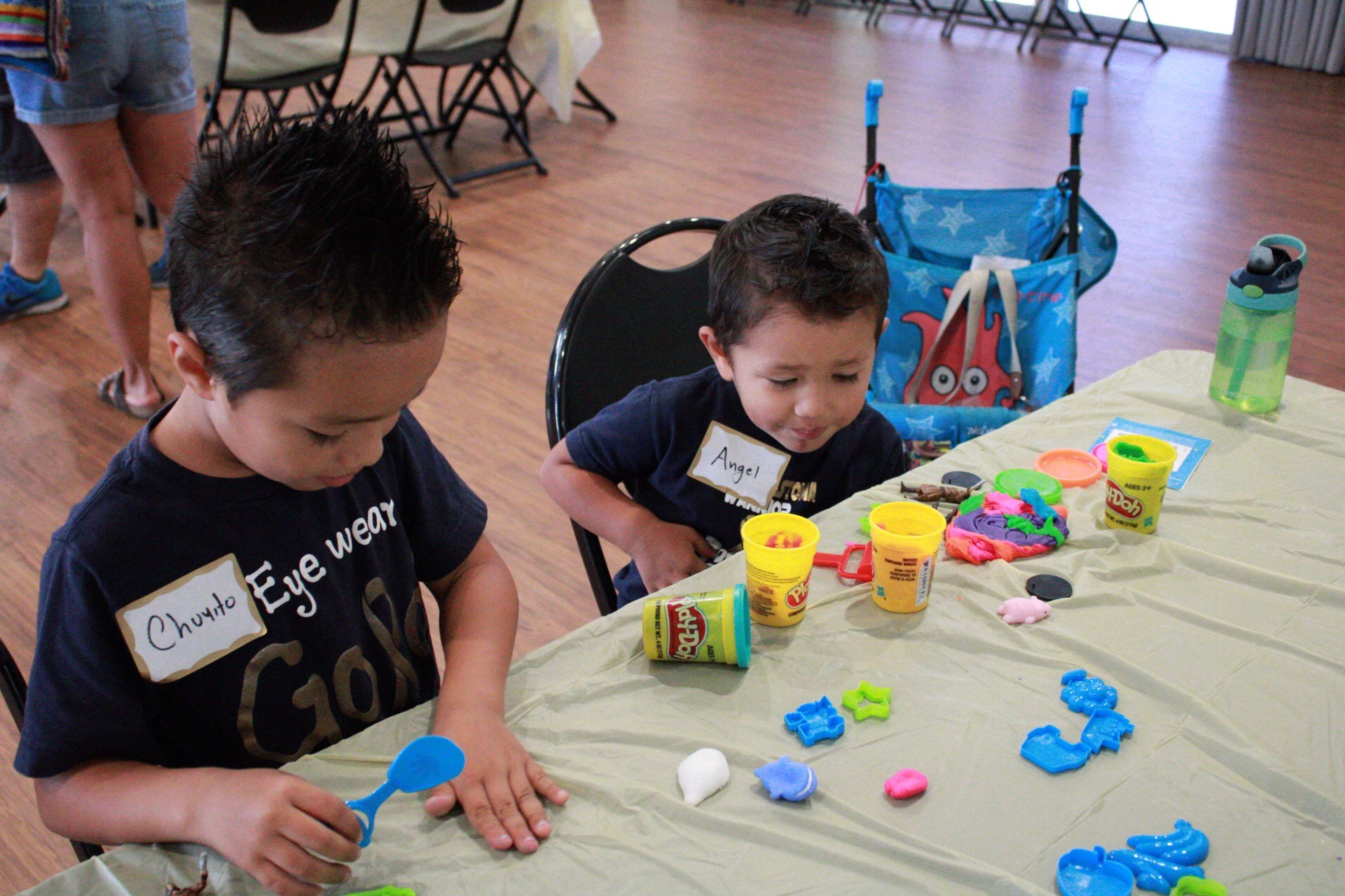 "Two boys, in matching shirts that read ""Eye Wear Gold"", sit at a table and create with Play-Doh. They are using plastic shapes and various colours of dough."