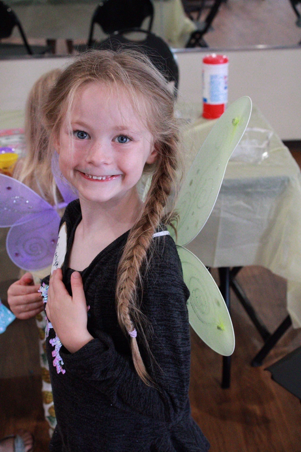 A young girl wears a huge smile and green fairy wings.