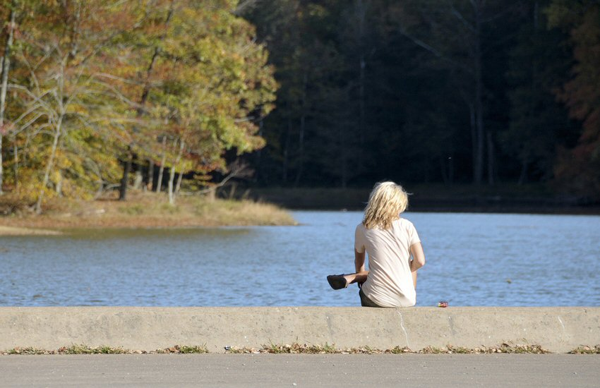A woman sits alone at a lake, bathed in sunlight. Ahead of her across still water, foliage to her left is sunlit. Trees further away stand in dark shadow.