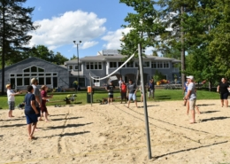 A group of teenagers enjoy a game of volleyball on a sand court surrounded by trees, under a cloud-dusted blue sky.