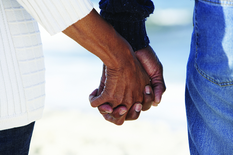 Two hands clasped together as the couple stand together. Through the gap between them, we have the impression of a blue sky and sea, and white sand.