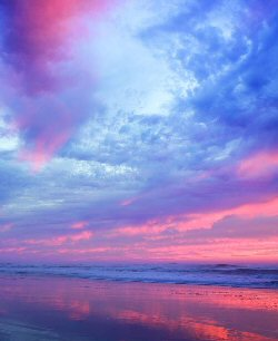 Colourful clouds merge from purple through pearly white, blue, pink, rose and peach, meeting the horizon and their reflection in the calm, wide ocean.