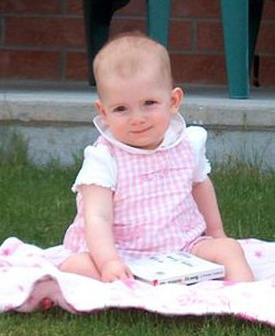 A young girl, bald from chemotherapy, relaxes on the grazz.