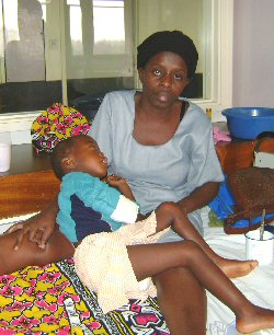 A mother sits with her very sick child in hospital.