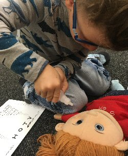 A young boy practices giving eye drops to a medical play puppet.
