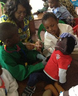 A boy learns about enucleation and prosthetic eyes with the help of a medical play puppet, in preparation for surgery.