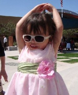 Young Grace models her beautiful pink dress and shades protecting her seeing eye.