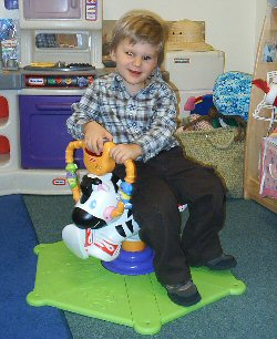 Smiling child sitting on an activity toy