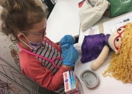 A young girl wearing medical gloves, glasses and a stethascope prepares to practive a procedure on a medical play puppet.