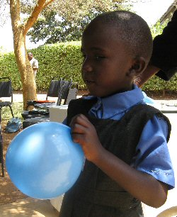 A bald Kenyan girl clutches a blue balloon