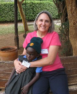 A volunteer hugs a young child on a swing seat in Kenya.