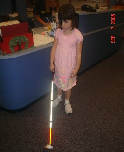 A young girl explores with her white cane.