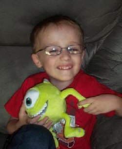 A grinning boy wearing glasses holds a Diseney toy Mike, the monocular character from Monsters Inc.
