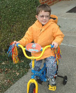 A young Rb survivor rides his bike with bright streamers tied to the handlebars.