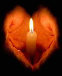 Two hands cupped together hold a single lit candle. The hands fade into shadow at the wrists, giving the impression of a heart shape formed around the candle.