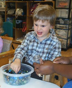 In a classroom, a young boy explores a tub containing coloured stones. The hands of an assistant are visible in the bottom right corner of the picture.