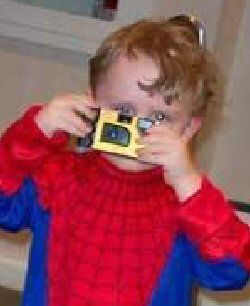 Child with camera and white reflex in eye