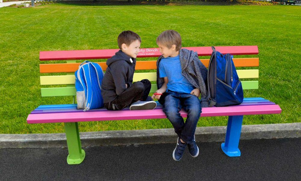 Two boys sit on a bench painted in bright rainbow colours, a wide lawn and trees behind them. One boy sits sideways with his legs crossed, leaning on his bag. The other leans against the back of the bench, legs stretched out to the ground, one ankle crossed over the other, turning in towards the other child. They appear to be deep in conversation.