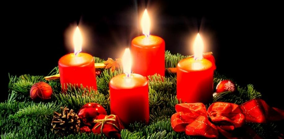 Four Christmas candles glow brightly against a black background, nestled in an Advent wreath of foliage, pine cones, and berries.