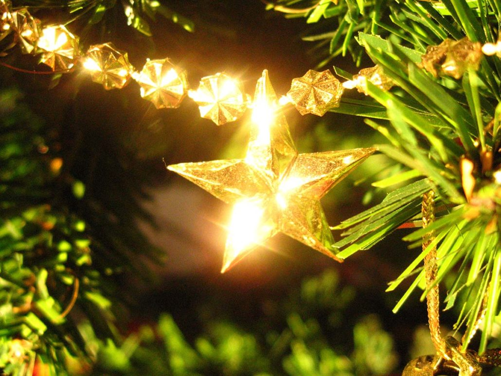 A close up image of a star hanging below a glowing golden garland, among Christmas Tree foliage.