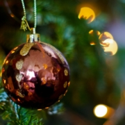 A crimson bauble hangs in focus, golden fairy lights reflected in its shiny surface, one glowing particularly white. The tree and lights are blurred in the background.