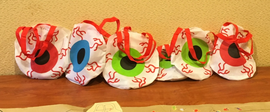 Six circular gift bags decorated as big colourful eyes are lined up on a shelf.