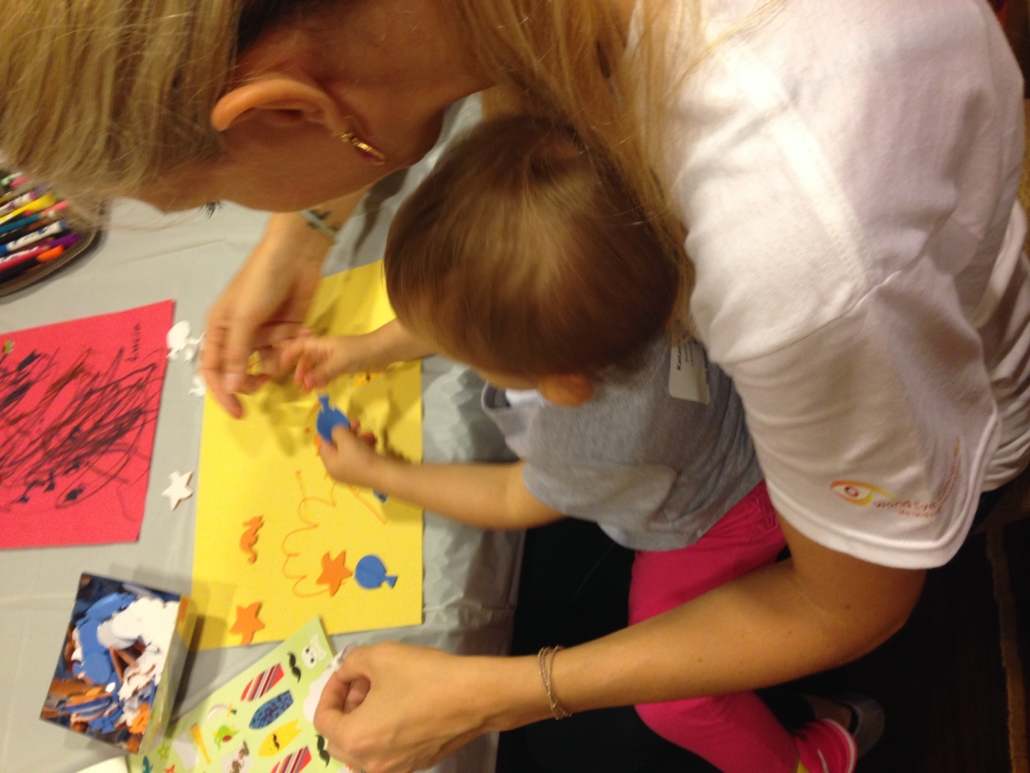 Morgan helps a young girl with her art project.