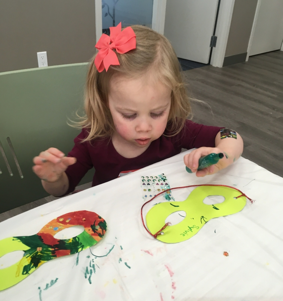 A young girl decorates a green superhero mask with markers and stickers.