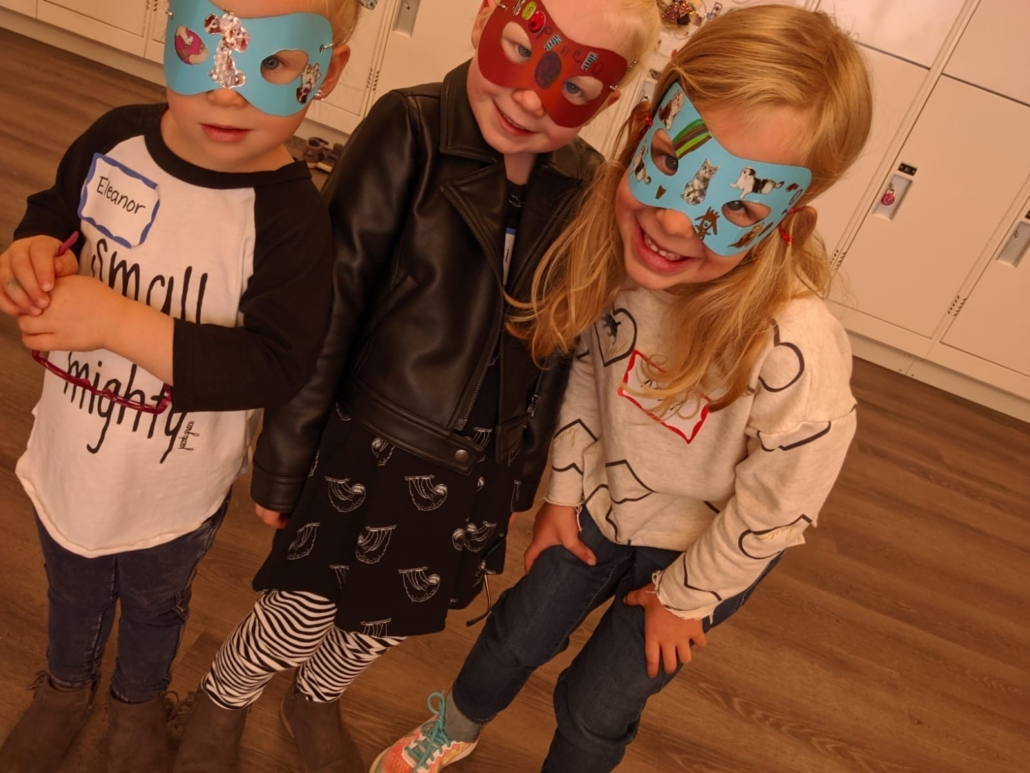 A group of children smile while modeling their decorated superhero masks.