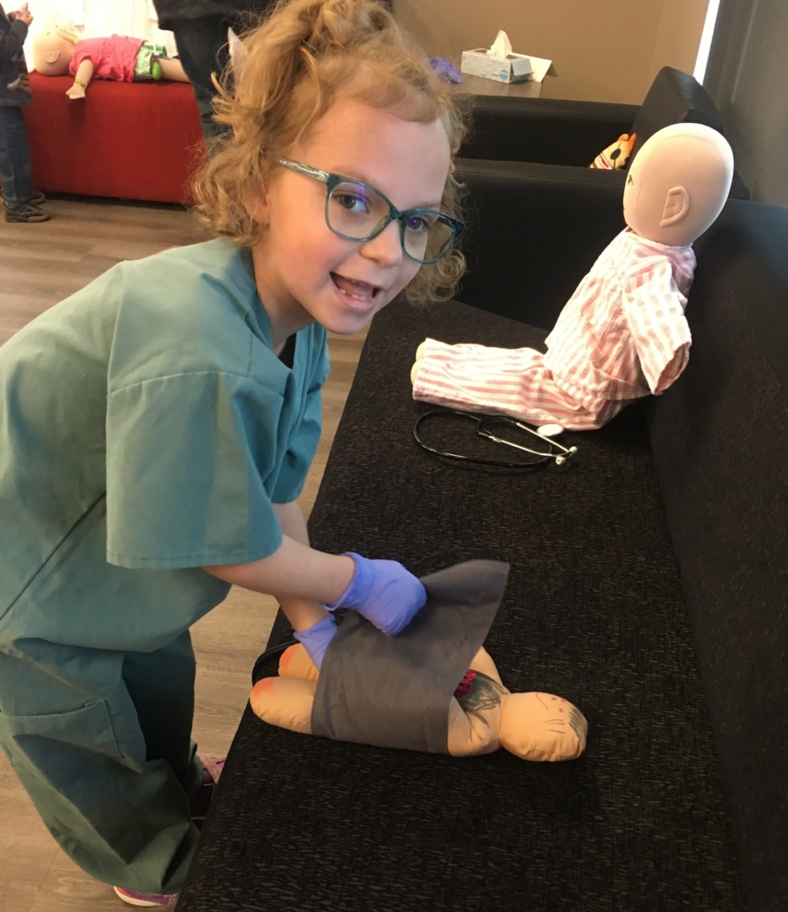 A young girl wearing medical gloves and scrubs wraps her cloth doll in a blood pressure cuff. Sitting in the background is another medical play doll.