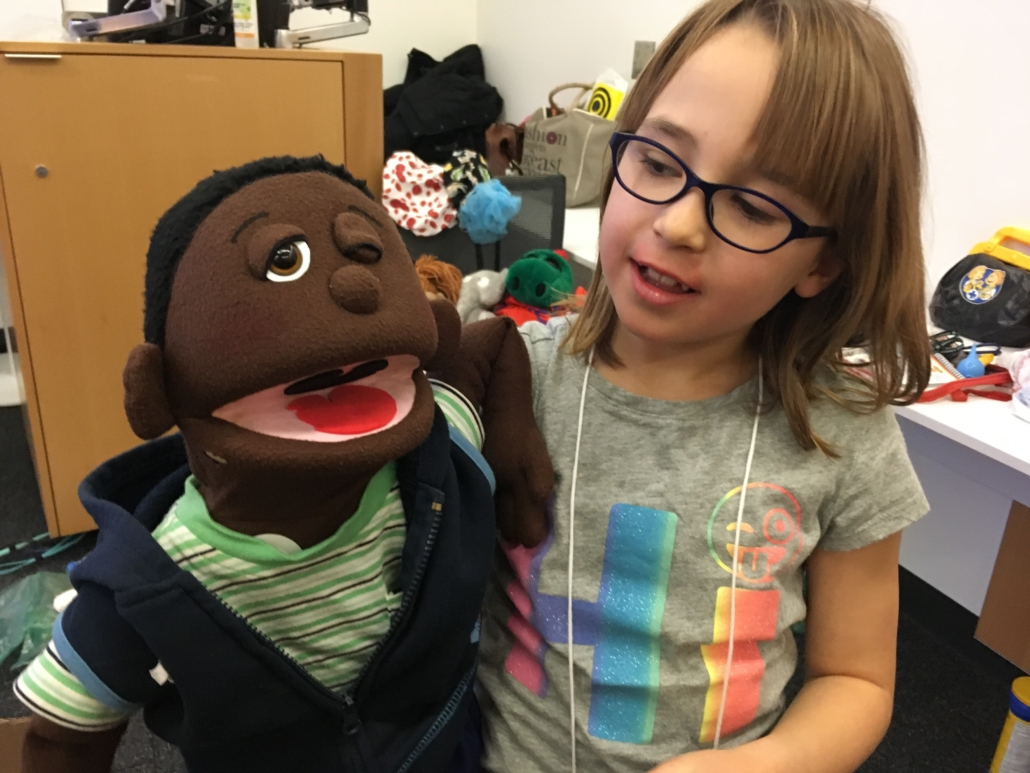 A young girl wearing glasses poses with Kamau after removing his eye. She is smiling.