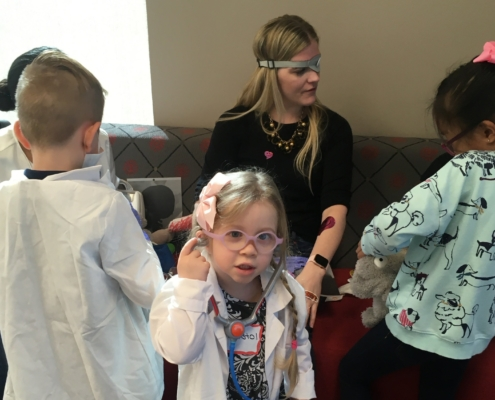 A female adult plays patient, cared for by a group of children dressed in medical outfits. She wears an eye patch on her left eye, and the children put bandaids on her arms. One of the children is wearing an anaesthetic mask.
