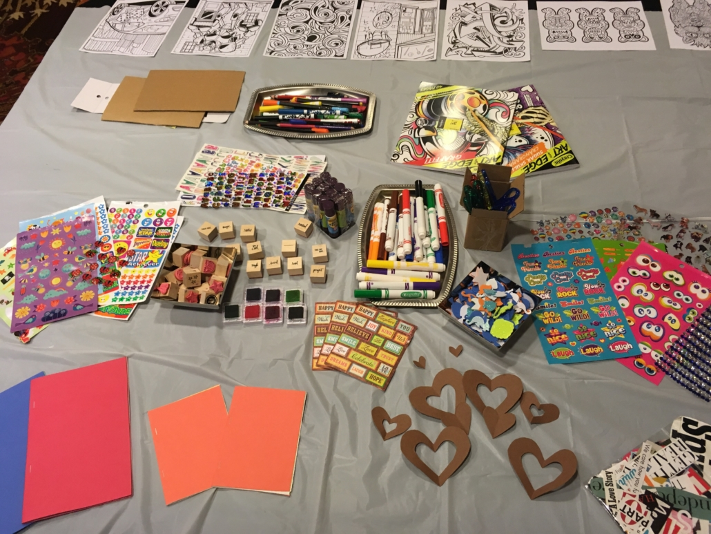 • Collage materials, stickers and stamps are laid out on a table