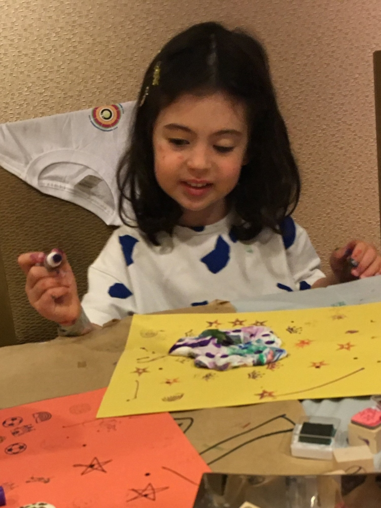 A young girl decorates a clay art project.