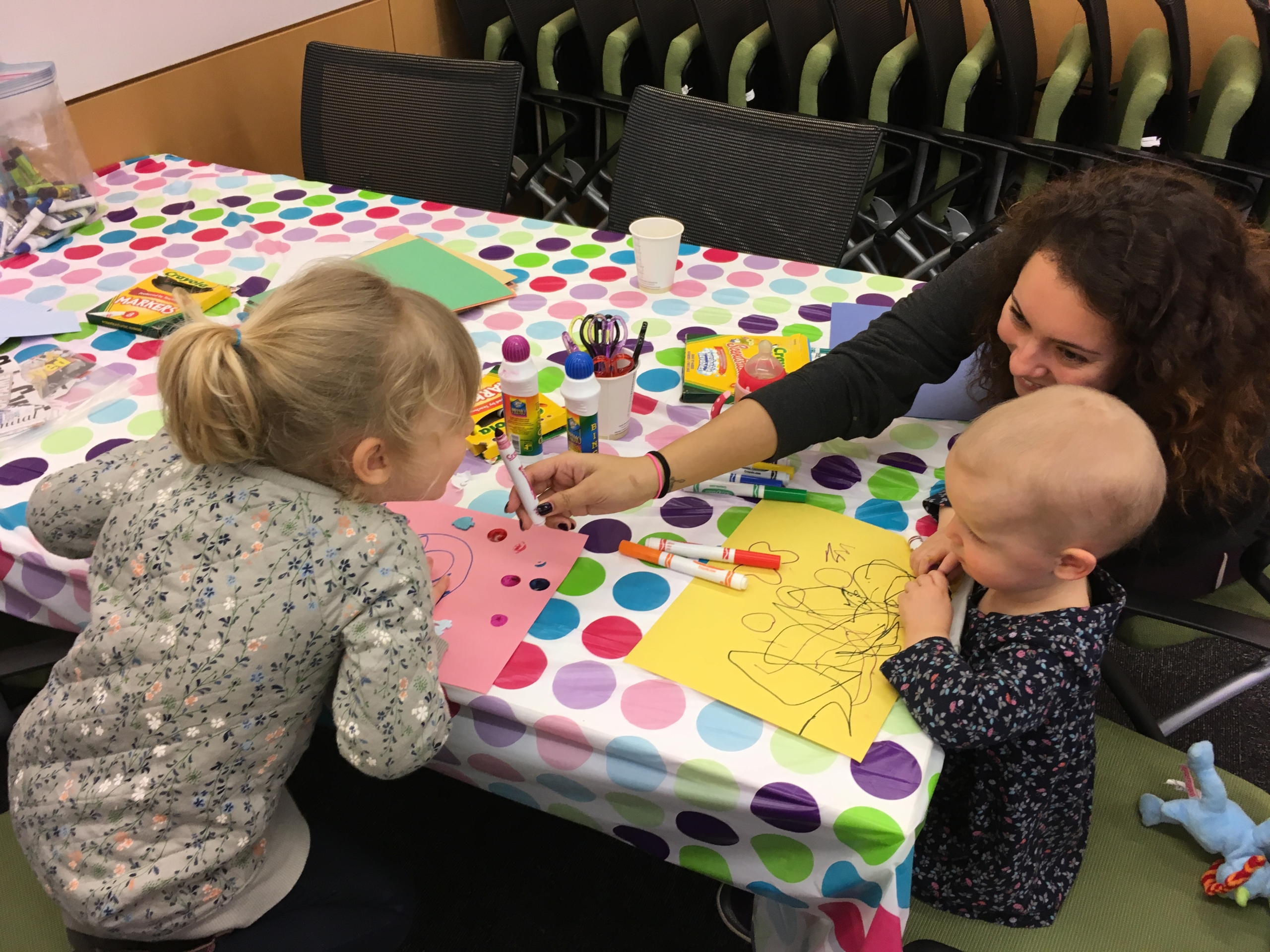 A child life intern helps two young girls with their personal story book projects during a retinoblastoma child life program in Toronto, Canada.