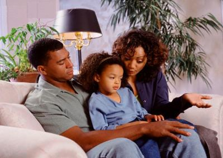 A child sits tucked between both parents, who are turned attentively towards the child as they talk.