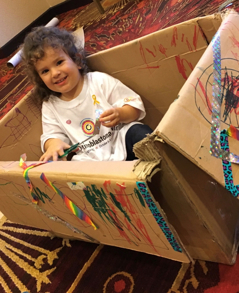 A young girl sits smiling in a decorated box - plane. boat. car. train...
