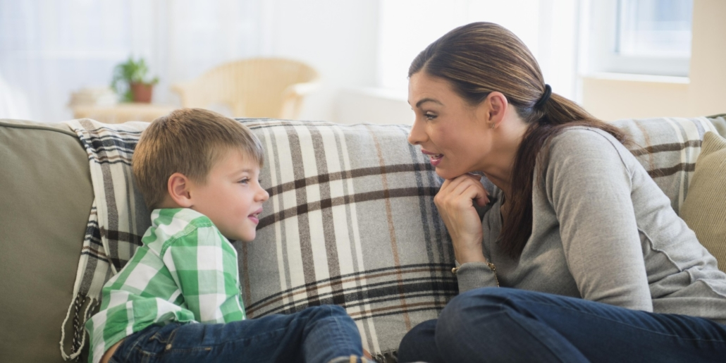 A mother and young child face one another oon couch while talking.