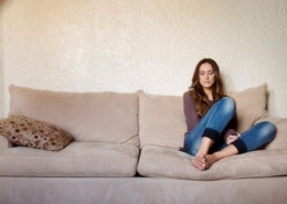 A woman sits alone on a couch at home.
