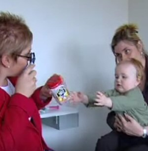 an optometrist holds an ophthalmoscope up to her eye with one hand to examine a child's eye, while holding a toy out with her other hand to keep the child focused in her direction.