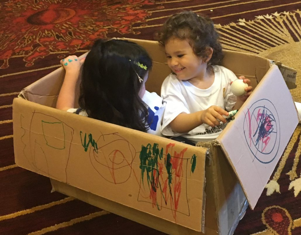 Two young girls sit facing one another in conversation, in a giant box they are decorating. The box became a plane, a boat, and a car.
