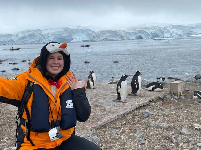 Marissa smiles and waves to the camera, dressed in an orange and black polar jacket and penguin hat. Behind her, penguins gather at the shoreline of a beach, and across the bay, ice and mountains can be seen in the distance.