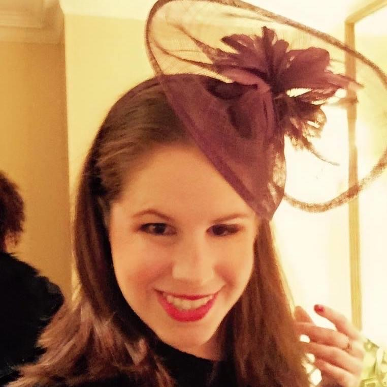 Marissa, smiling and wearing a fascinator