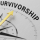 "The gold pin on a compass points to the word ""survivorship"""