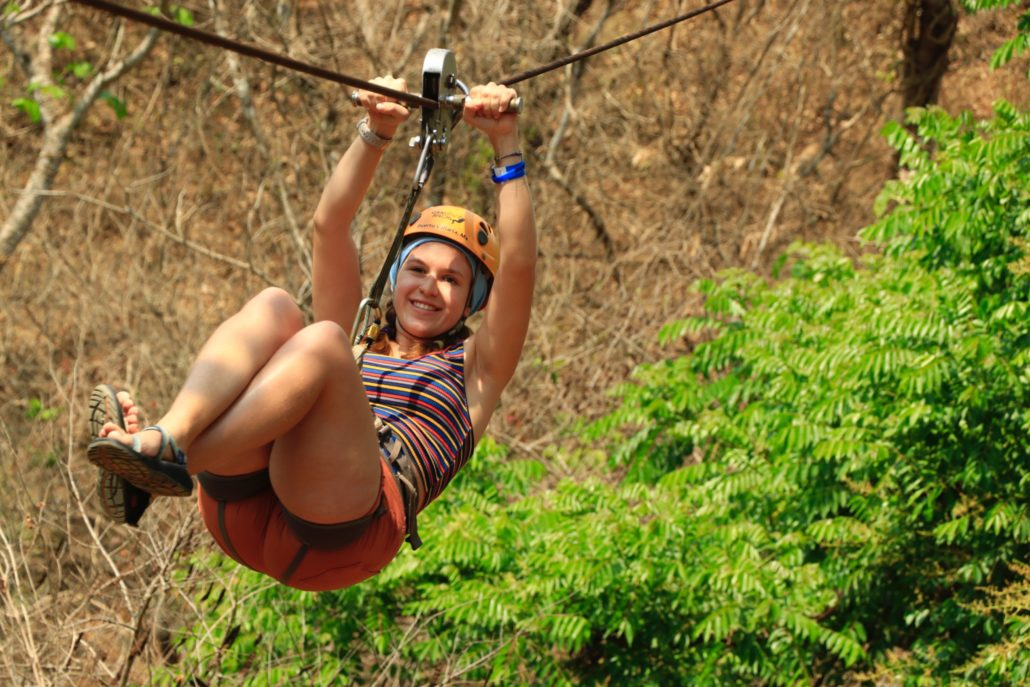 A young female Rb survivor smiles broadly while ziplining