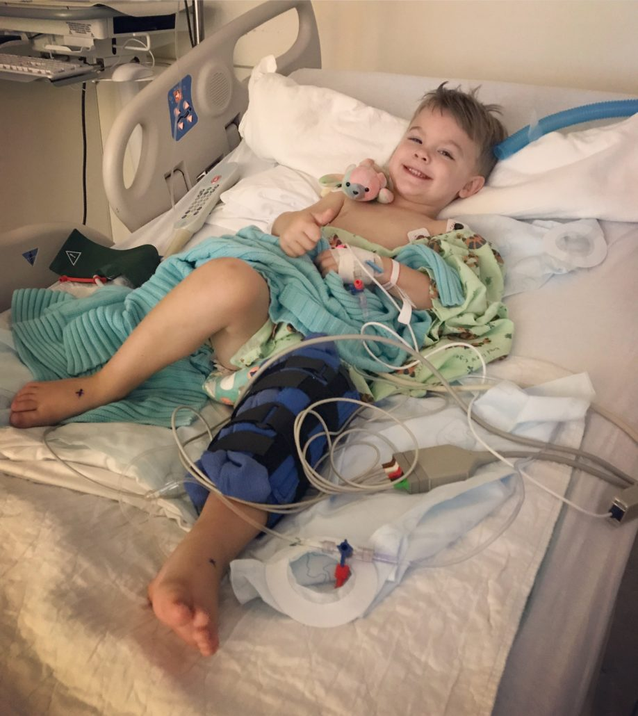 A young boy lying in hospital bed gives a thumbs up. He is wearing hospital gown and attached to many monitors.