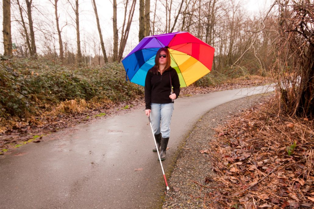A woman wearing sunglasses walks along a rainy path, holding a white cane in one hand. In the other hand, she holds a large rainbow coloured umbrella, open to provide shelter from the rain.