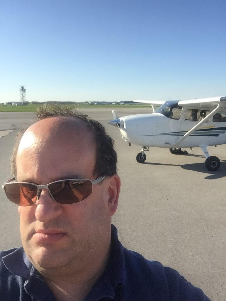 Brian at the airfield, his plane in the background.