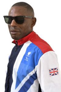 Darren, posing in profile, wearing dark glasses and his Olympics 2012 Team GB jacket.